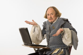 William Shakespeare in period clothing sitting in school desk with laptop computer.