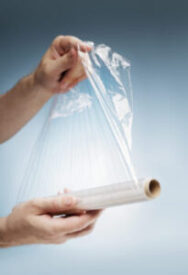 Stock Photo of man holding a sheet of clear plastic wrap